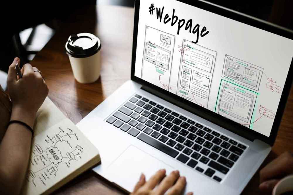 Crear página web - Escritorio laptop libreta con ideas manos y café