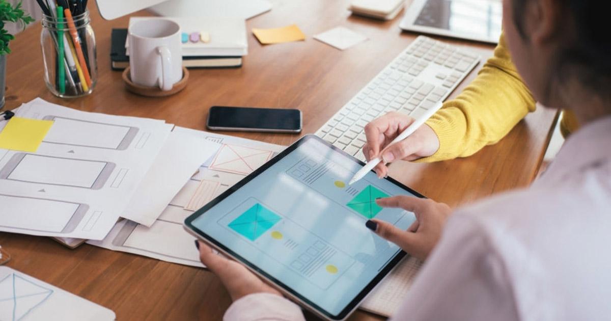 Dos diseñadores web reunidos revisando un proyecto a realizar